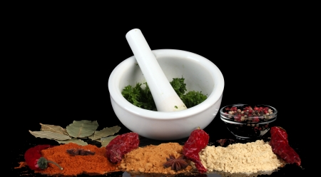Composition of White mortar and pestle with spice and vegetables isolated on black photo