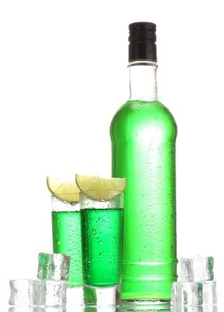 ajenjo: botellas y vasos de absenta con lim�n y hielo aislados en blanco