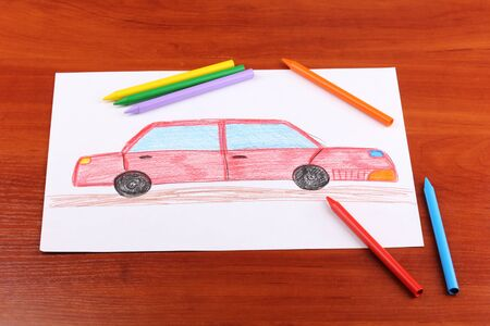 Childrens drawing of red car and pencils on wooden background photo