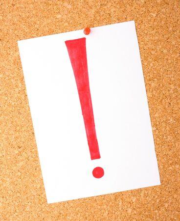note of exclamation: Nota blanca con signo de exclamaci�n en el tablero de corcho Foto de archivo