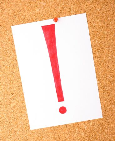 note of exclamation: White note with exclamation mark on cork board