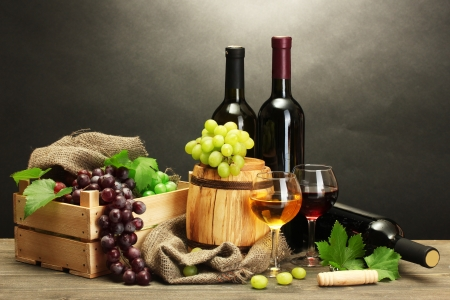 vine leaf: barrel, bottles and glasses of wine and ripe grapes on wooden table on grey background Stock Photo