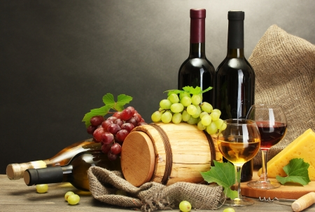 barrel, bottles and glasses of wine, cheese and ripe grapes on wooden table on grey background Stock Photo - 14111497