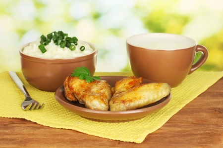 Mashed potato in the bowl and roasted chicken wings in the plate and cup with milk on colorful napkin on wooden table close-up photo