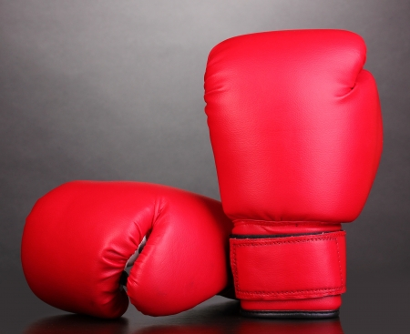 Red boxing gloves on grey background photo