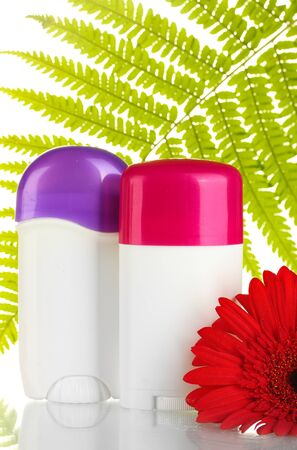deodorants with flower and green leaf isolated on white photo