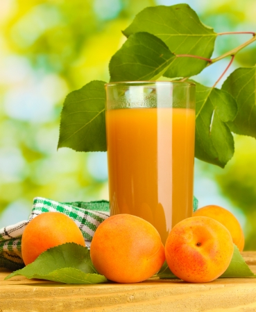 glass of apricot juice and fresh apricots on wooden table on green background photo