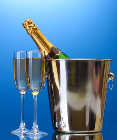 Champagne bottle in bucket with ice and glasses of champagne, on blue background photo