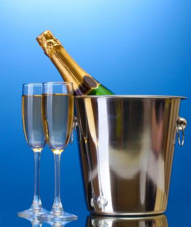 Champagne fles in emmer met ijs en glazen champagne, op blauwe achtergrond