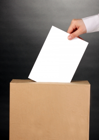 Hand with voting ballot and box on grey background Stock Photo - 14110790
