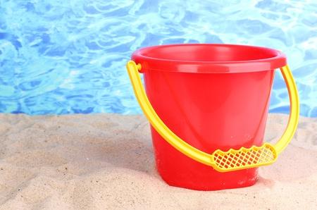 Childrens bucket on sand on water background photo