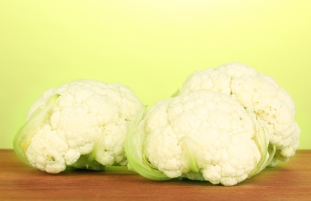 Fresh cauliflower on wooden table on green background photo