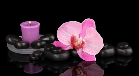 Spa stones with orchid flower and candle isolated on black photo