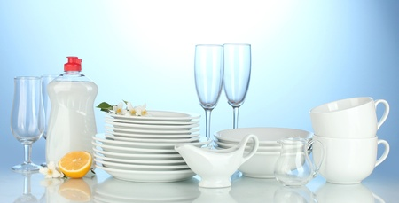empty clean plates, glasses and cups with dishwashing liquid and lemon on blue background Stock Photo - 14169662