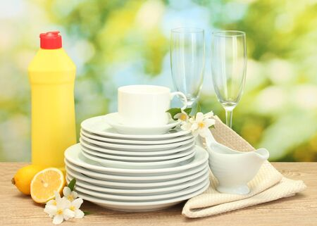 empty clean plates, glasses and cups with dishwashing liquid and lemon on wooden table on green background photo