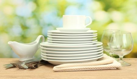 empty clean plates, glasses and cup on wooden table on green background photo