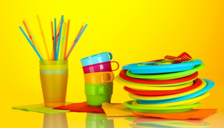 bright plastic disposable tableware on colorful background photo
