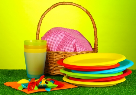 bright plastic disposable tableware and picnic basket on the lawn on colorful background photo