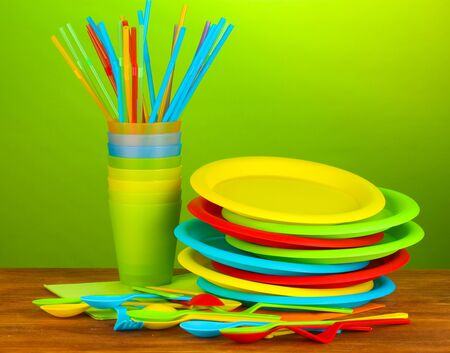 bright plastic disposable tableware on wooden table on colorful background photo
