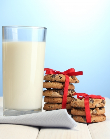 glass of milk and chocolate chips cookies with red ribbon on wooden table on blue background Stock Photo - 14170272