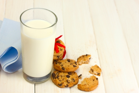 glass of milk and chocolate chips cookies with red ribbon on wooden table photo