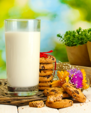 glass of milk, chocolate chips cookies with red ribbon and wildflowers on wooden table on green background Stock Photo - 14173422