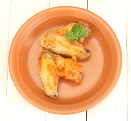 roasted chicken wings with parsley in the plate on white wooden background close-up photo