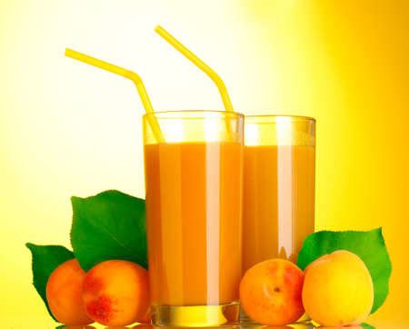 glasses of apricot juice on yellow background Stock Photo - 14162151