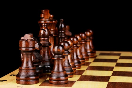 Chess board with chess pieces isolated on black photo