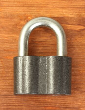 old padlock on wooden background close-up photo