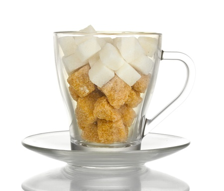 white refined sugar and Lump brown cane sugar cubes in glass cup isolated on white photo