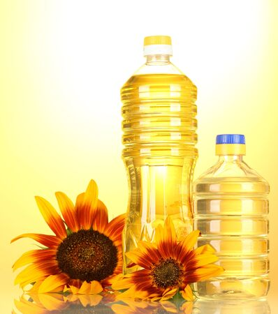 sunflower oil and sunflowers on yellow background Stock Photo - 14170138