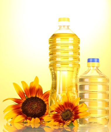 sunflower oil and sunflowers on yellow background  photo