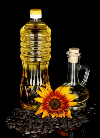 sunflower oil in a plastic bottle and small decanter isolated on black background photo