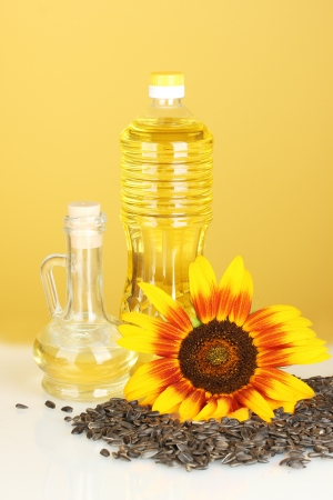 sunflower oil in a plastic bottle and small decanter on yellow background photo