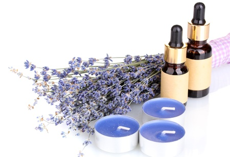 Lavender flowers with aroma oils and candles isolated on white photo