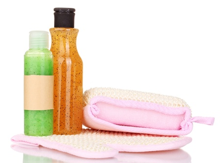Bottles with scrub and sponges isolated on white photo