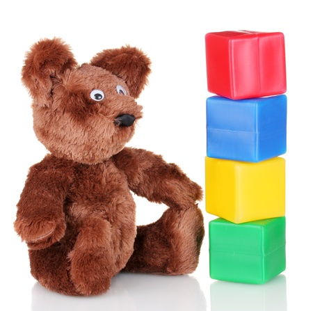 Sitting bear toy and color cubes isolated on white photo
