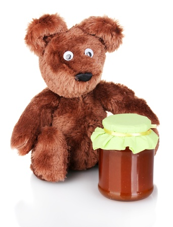 Bear toy and sweet jam isolated on white photo