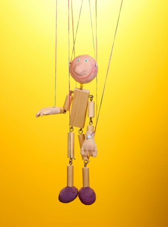 Wooden puppet on yellow background photo