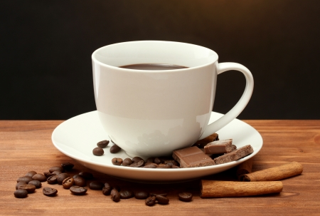 cup of coffee and beans, cinnamon sticks and chocolate on wooden table on brown background photo