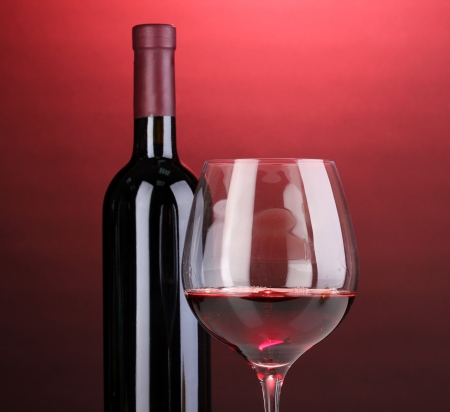 Bottle of great wine and wineglass on red background photo