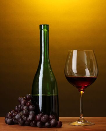 Composition of wine bottle and wineglass on wooden table on brown background