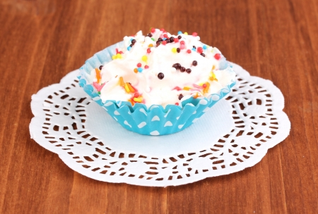 Creamy cupcake on wooden background photo