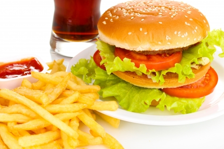 Big and tasty hamburger on plate with cola and fried potatoes close-up photo