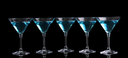 Blue cocktail in martini glasses isolated on black photo