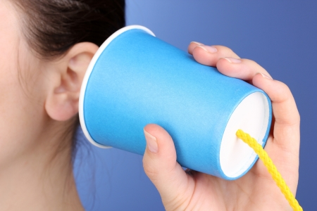 rumours: Human ear and paper cup near it close-up on blue background
