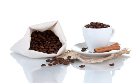 Composition of the cup with coffee beans isolated on white photo