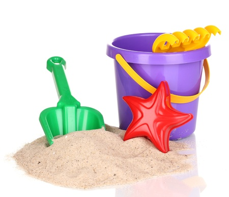 Childrens beach toys and sand isolated on white photo