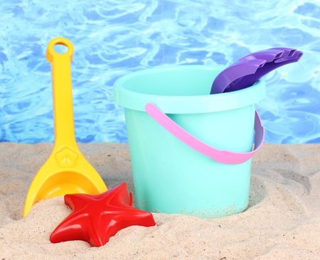 Childrens beach toys on sand on water background photo